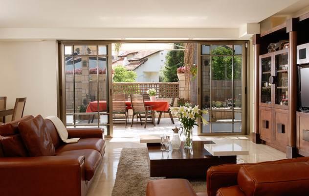 רהיטים שנבחרו על ידי בני הזוג עם מערכת גדולה לטלוויזיה ולאחסון וספות בגוון חום-אדמדם. סלון הבית (צילום:אסף הבר)