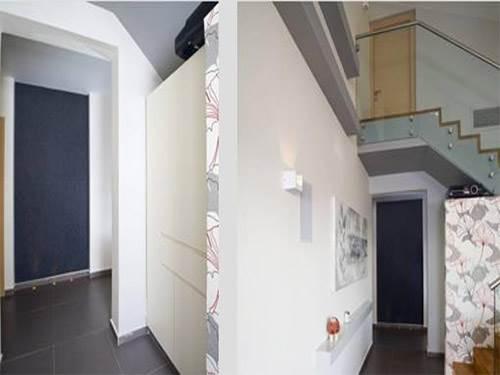 המראה של המסדרון מהסלון הודגש בטפט אפור כהה ותאורות לד מהרצפה. בנוסף, נהרסו הקיר והמעקה של המדרגות על מנת לחשוף את הגרם (צילום: טכנוגרפיקס, יניב שוורץ)