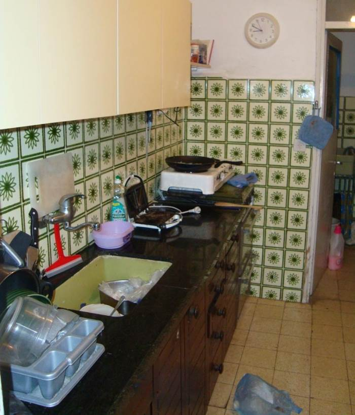 מטבח סגור וצר, קרמיקה ירוקה וארון עליון העשוי מפורמייקה. שיא הטרנדיות של המטבחים של שנות ה-60 וה-70.