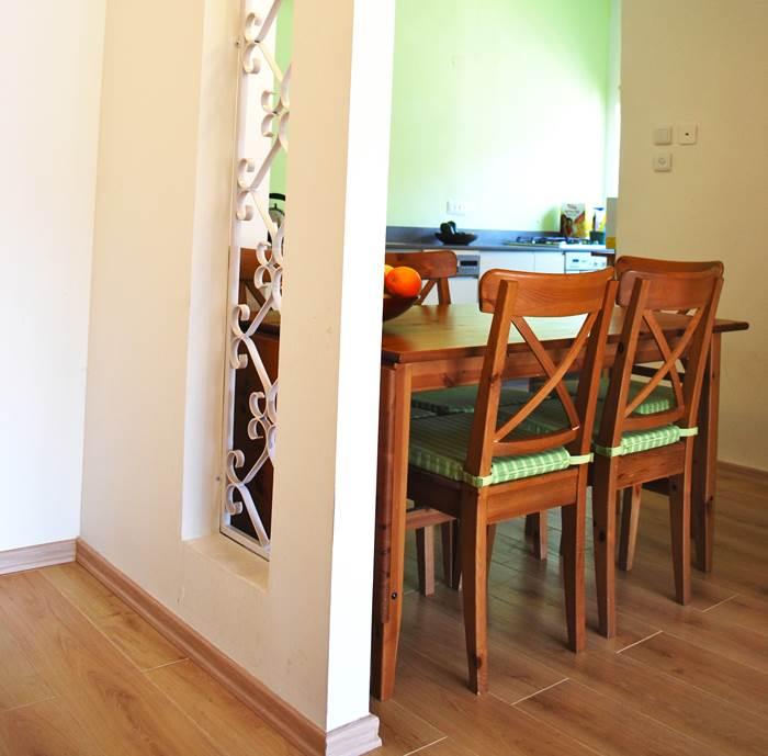 מבעד לסורגי המתכת הלבנים ניבט קיר המטבח. הכניסה אחרי (צילום: שירה גזית)
