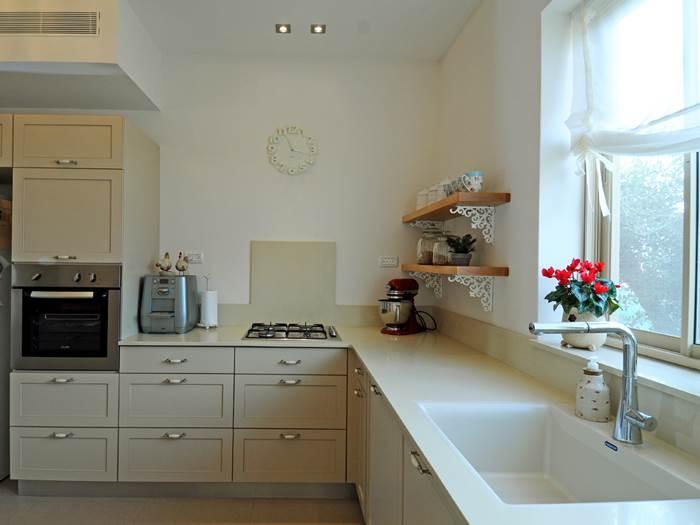 חיפוי השיש ממשיך כל הדרך מהמשטח ומטפס גם אל קירות החדר המטבח