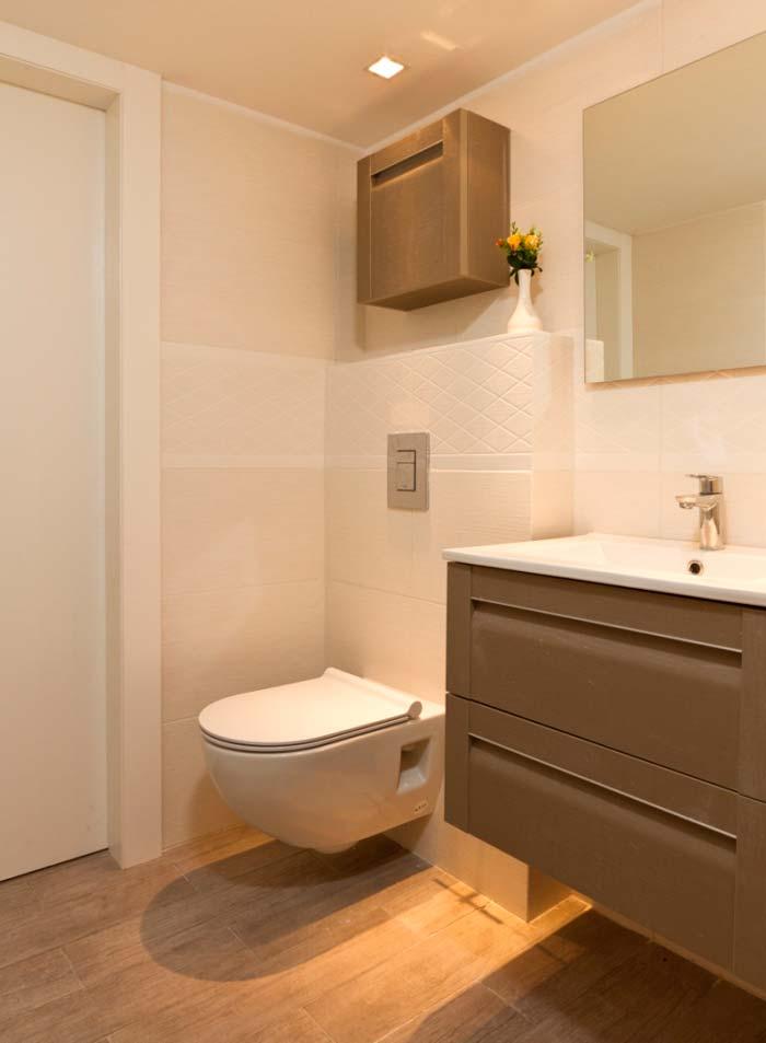 חדרי הרחצה מרוצפים אפור חם ועיטורים עדינים על גבי קירות לבנים וצחים