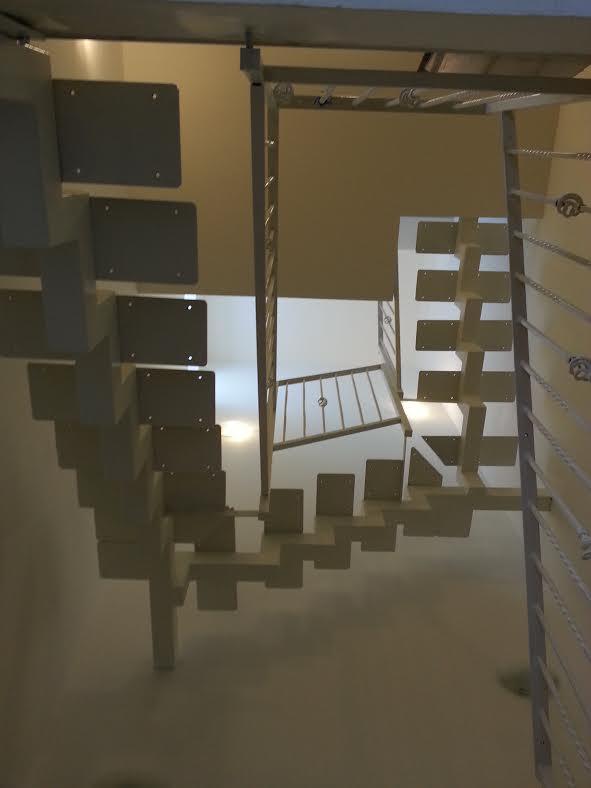 משטחי העץ המלא יוצרים המשכיות: גרם המדרגות שמוביל לעליית הגג