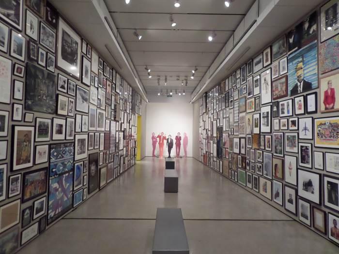 החלל המרכזי בתערוכה של Paul Smith עם אלפי תמונות, ציורים וצילומים ממוסגרים.