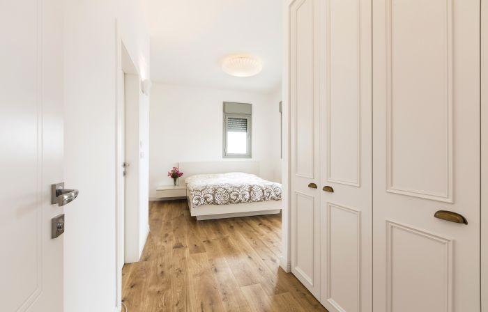 פרקט עץ טבעי על הרצפה למראה קלאסי: מבט נוסף אל חדר השינה של ההורים. פרקט: נגב, ארונות: ארונא