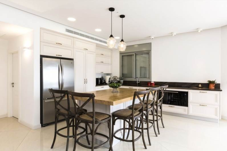 """עיצוב קלאסי, אך לא מכביד. מבט אל המטבח. מטבח: אביבי, כסאות בר ותאורה: ביתילי, דלתות פנים: פנדור דגם """"יוניק"""", ריצוף: נגב"""