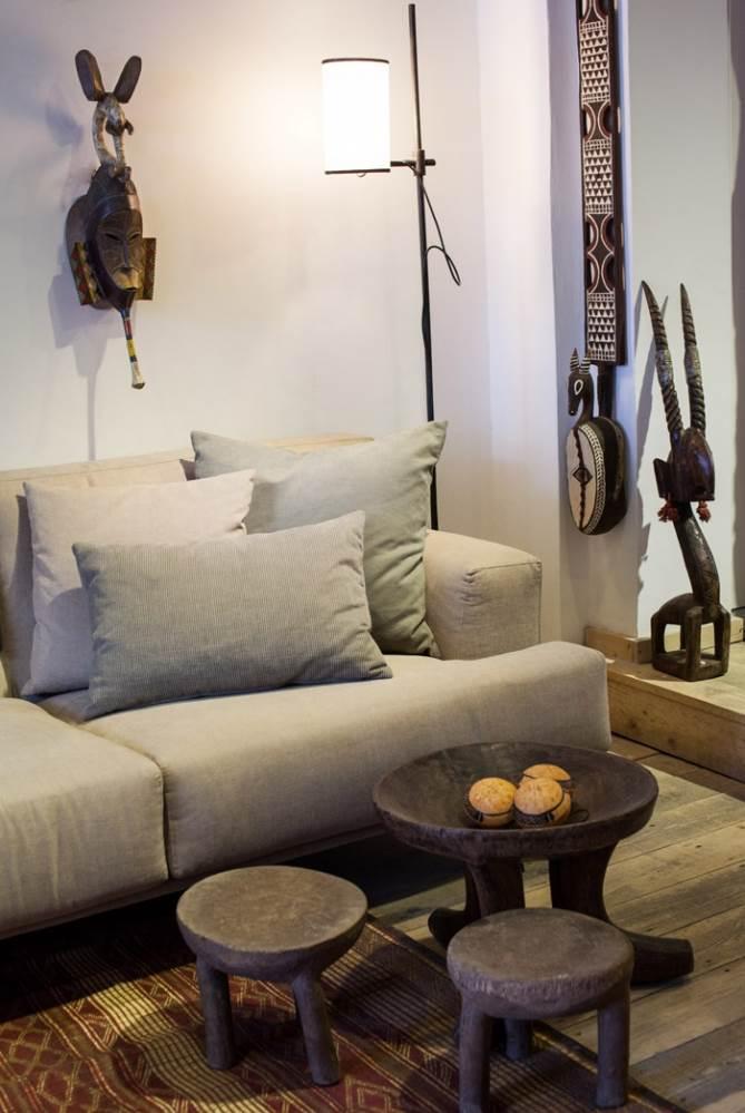 שרפרפי עץ מאתיופיה בעבודת יד לצד ספה מפנקת מרובת כריות, שטיח קש מניג