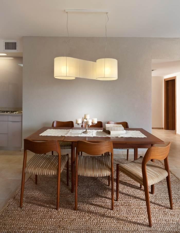 פינת אוכל עם קיר בשליכט ייחודי ותאורה מעוצבת ודומיננטית