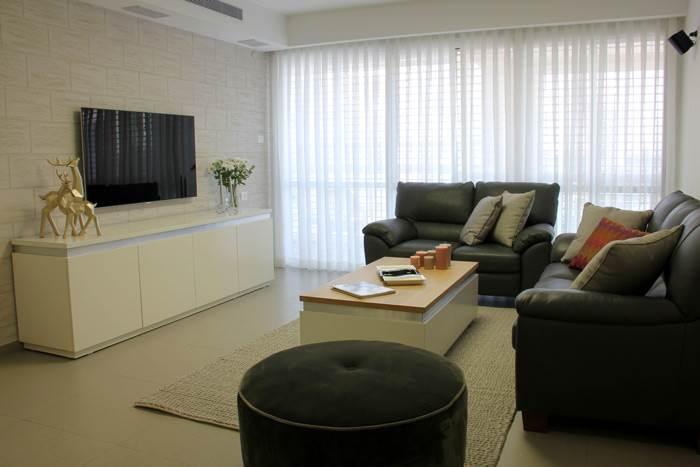 מבט על הסלון המעוצב עם קיר המדמה לבנים ירושלמיות