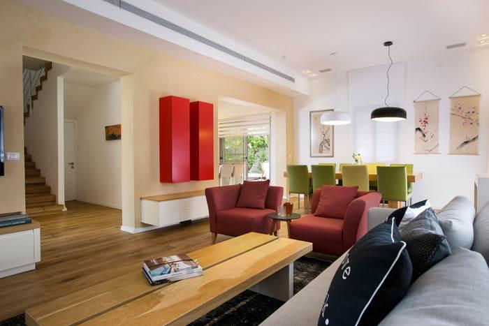 הסלון עוצב במראה חמים עם משחקי צבעוניות על גווני אדום, ירוק ומנעדים של אפור