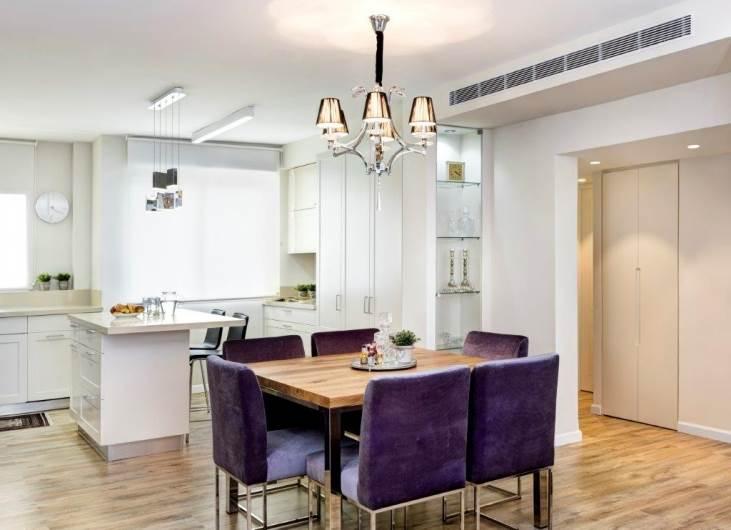 למטבח נוספה תאורה מתאימה וידיות שממשיכות את הקו הנקי: מבט על המטבח ופינת האוכל
