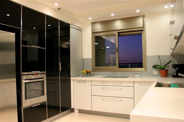 המטבח פתוח למחצה ומעוצב בצורה שבה הוא נראה ולא נראה גם יחד, (צילום: ירון עטיה)
