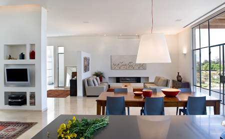 הקירות המנותקים מגדירים את מבואת הכניסה ופינת המשפחה. מבט ממטבח הבית אל הסלון הפתוח (צילום: עמית גושר)