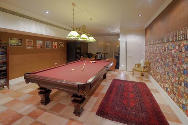 מקום ההתכנסות של המשפחה אשר עוצב כבר אפלולי עם שולחן ביליארד גדול במרכזו ופינת טלוויזיה מפנקת. (צילום: נעם ארמון)