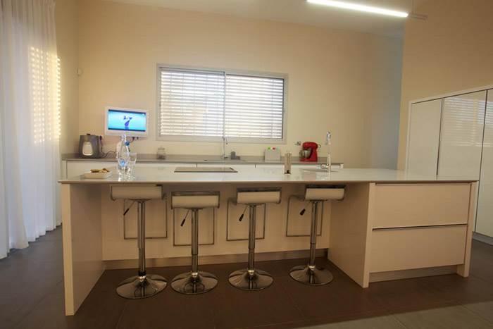 מטבח מודרני בקו נקי עם ידיות ומוצרי חשמל אינטגרליים. (צילום: דרור כץ)<br/>