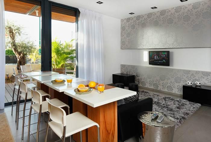 חדר המשפחה והמטבח חולקים את אותו חלל אך נבדלים בסגנון עיצובי שונה. מבט על פינת המשפחה והאיים אשר עיצב מיטלמן.  (צילום: שי אפשטיין)