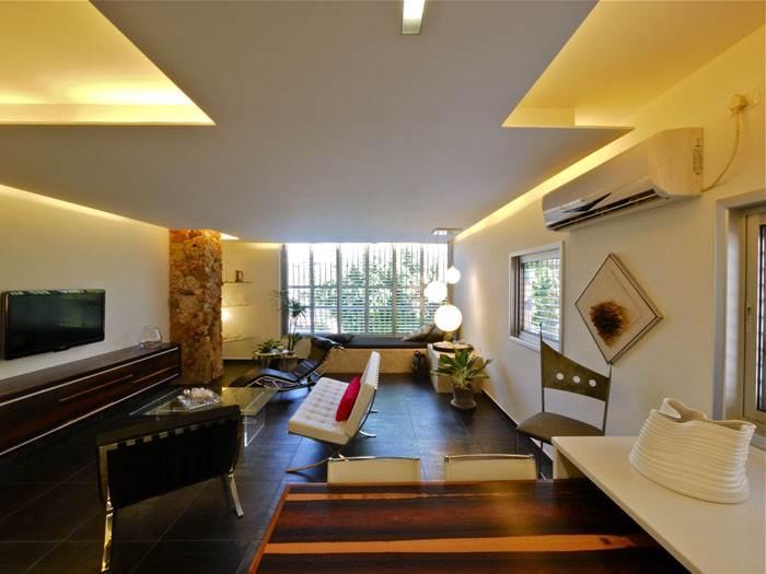 סלון הדירה לאחר השיפוץ. קווים נקיים, ריהוט מודרני ושפע של אור. (צילום: איתי סיקולסקי)