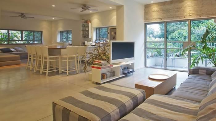 גוונים של לבן ואפור ושילוב של חומרים דומיננטים כמו בטון לצד עץ. מבט לאזור הסלון והמטבח (צילום: דרור כץ)