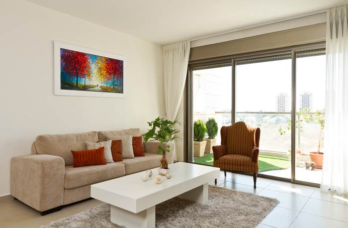 כריות, ציור שמן ססגוני וכורסא שכמעט ונזרקה לפח. פינת הישיבה בסלון