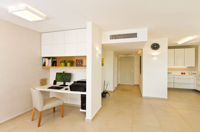 פלטת עץ מרחפת בשילוב עם ארון פורמייקה לבן, המסתיר מאחוריו את הקטלוגים הרבים של בעלת הבית. פינת העבודה