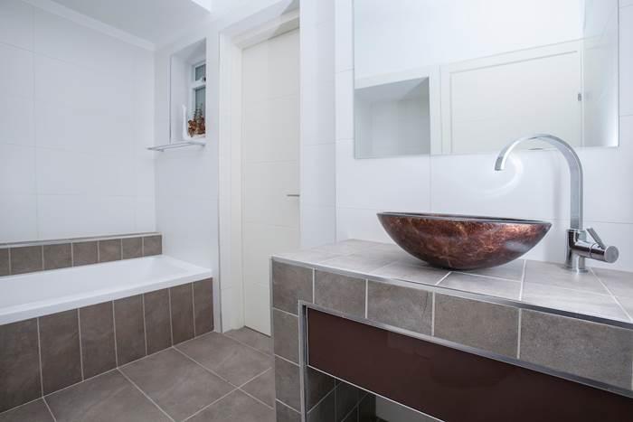 חדר שירותים נוסף מעוצב בגוונים חומים ומשודרג באמצעות פריטים ייחודיים