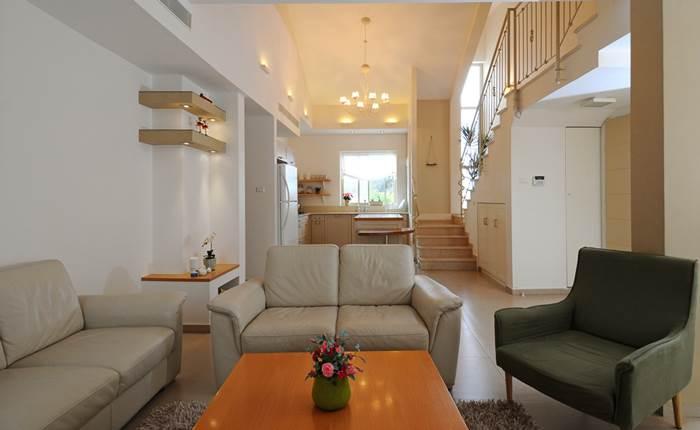 ספות הקרם והכורסא הירקרקה מוסיפות חמימות. מבט נוסף לחלל הסלון