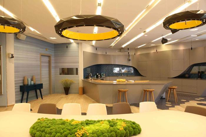 פינת האוכל בבית האח הגדול - גופי תאורה המעוצבים כטבעות משוננות ותוחמים את השטח