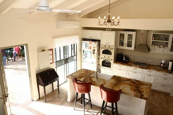 הצצה לעבר המטבח המעוצב עם אי במרכזו ומשטח שיש ייחודי שבחרו בעלי הבית