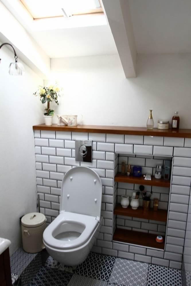 חדר הרחצה מתכתב עם קיר הלבנים החשוף שבבית בעזרת חיפויי הקירות ואריחי הריצוף