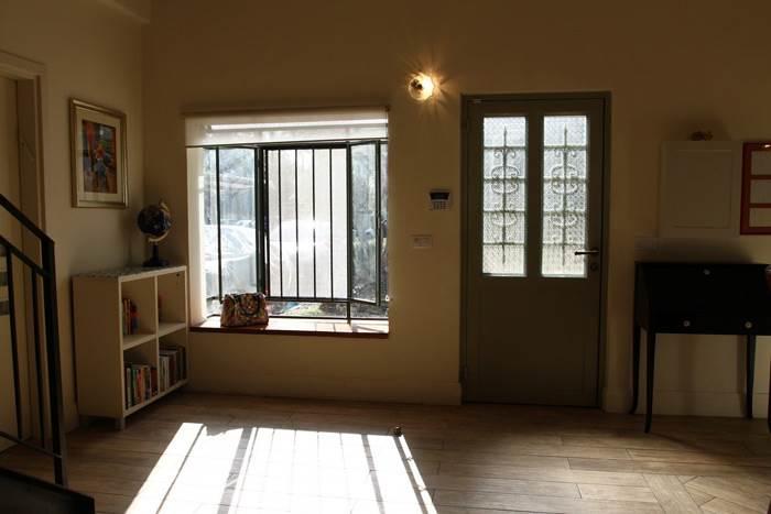 מבואת הכניסה עם חלונות ברזל בלגיים שחוזרים גם בשאר הבית ומותירים רושם עכשווי