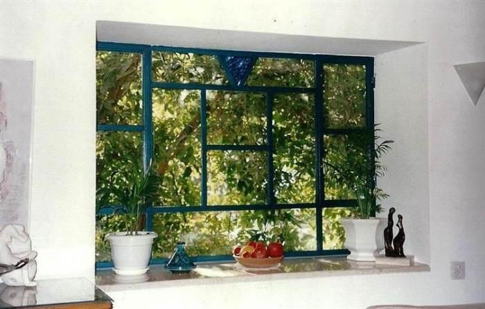 חלון בלגי נפתח בצבע אפור, המחולק לחלונות מלבניים. מבית רוםסן - אומנות הפרופיל הבלגי