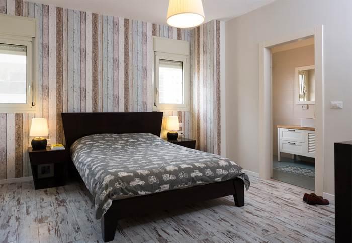 חדר השינה קיבל עיצוב כפרי במיוחד עם פרקט עץ מולבן וטפט פסים בהתאמה