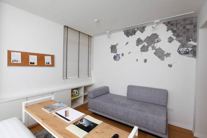 רימה ארסלנוב, ללא כותרת, גבס, רישום על קיר, 2014. העבודה מהווה עדות לקיר אורנומנטלי העשוי מאלמנטים מוקטנים של משרביות המבצבץ מהקיר.<br/>