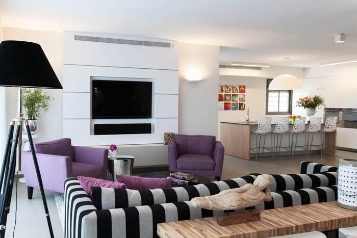 מבט על הסלון המעוצב בגוונים מונוכרומטיים בשילוב סגולים