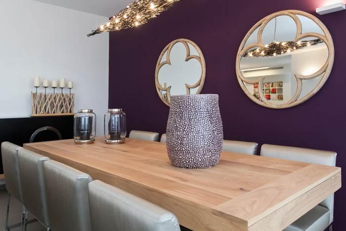 קיר פינת האוכל צבוע בסגול חמים עם מראות מעוצבות וגוף תאורה מרהיב
