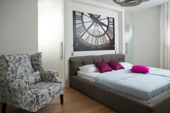 בחדר השינה שולב פרקט עץ ליצירת חמימות ואינטימיות ולצד המיטה דלתות בזכוכית מט המובילות לחדר הרחצה הצמוד לו