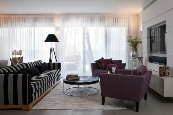 מבט על הסלון המעוצב עם וילונות רכים המותירים מקום לאור הטבעי לחדור אל הבית