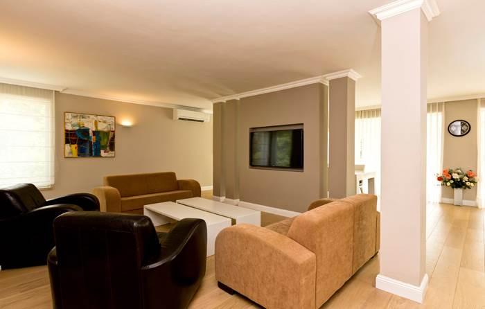 הסלון עם קירות בגווני מוקה וריהוט מונוכרומטי