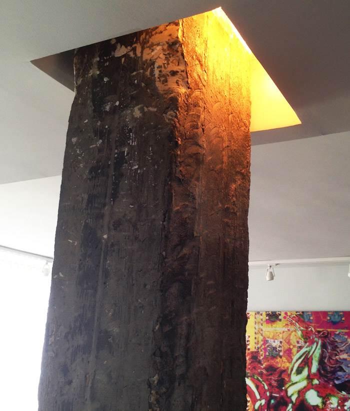 עמוד הבטון החשוף עם תאורה, שמדגישה את החומריות הגסה.
