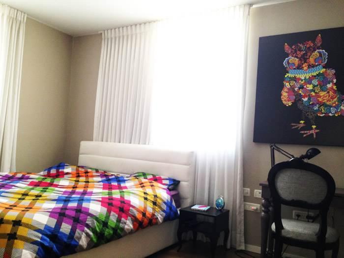 חדר השינה. חדר השינה חף מאלמנטים מיותרים. מיטה, קונזולה של חברת IKEA (עליה מונחים בגדים שלא היה כח לקפל) ושתי שידות צד. ליהי משתדלת להתאים את המצעים לתמונה הצבעונית בעיצובה. חדר ההורים הוא היחיד שנצבע בצבע אפור סגול רומנטי- השראה ממלון LANGHAM הלונדוני בו שהו בני הזוג. כדי לייצר סימטריה בחדר, הוילונות חורגים ממסגרת החלון הנתונה ונותנים אשליה של פתח אור רחב יותר. בצמוד לחדר השינה יש חדר ארונות עם אוסף הנעליים שלי ליהי.