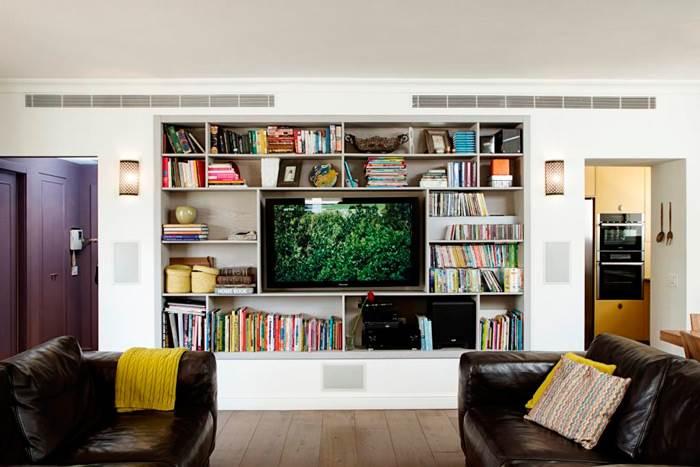 הקיר המרכזי בסלון נבנה כפתרון לצרכי אחסון וליצירת בידוד אקוסטי