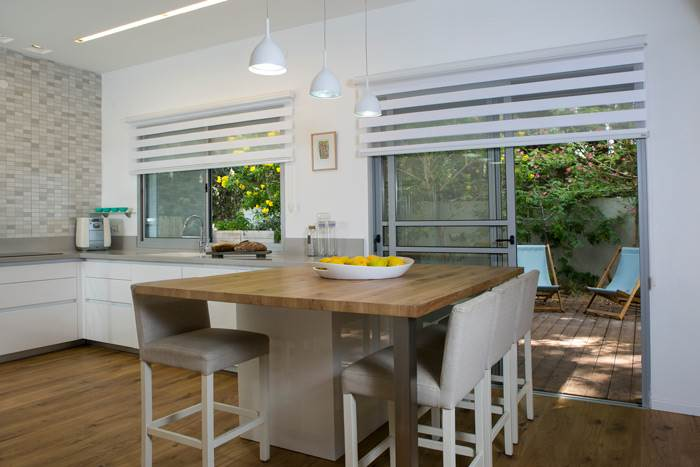 למטבח המעוצב התווסף אי מפלטת עץ אלון, המהווה נקודת מפגש מרכזית ומתכתב עם רצפת הפרקט<br/>