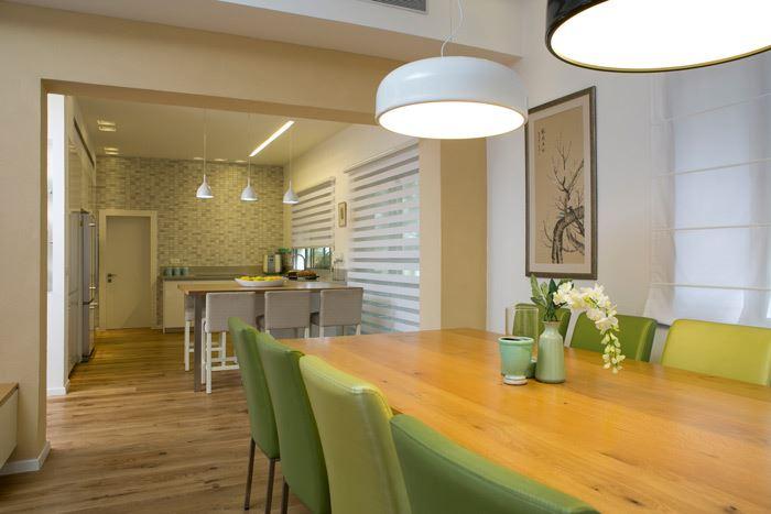 פינת האוכל המהודרת מוקמה בהמשך למטבח, עם סט כסאות בגוון ירוק בהיר וצמד גופי תאורה עגולים המשרים רוך ואינטימיות<br/>
