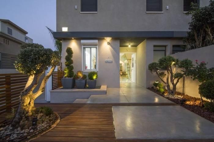 משטחים של דק ובטון ותאורת אווירה מתאימה: הכניסה מהחצר בשעות הערב