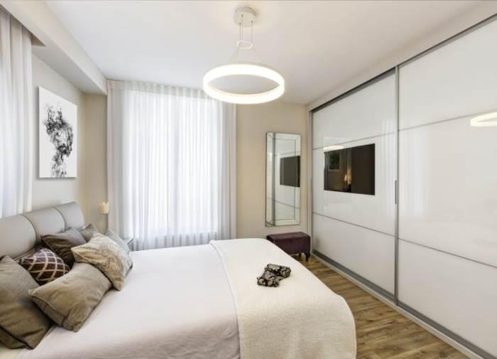 מיטה מתכווננת מפנקת עמוסה בכריות. מבט על חדר השינה