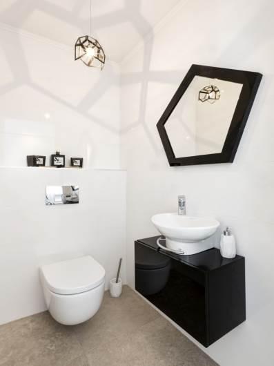 גוף התאורה יוצר צל ייחודי על הקיר: חדר שירותים
