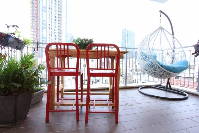 המרפסת הפונה לנוף האורבאני, רוצפה באריחי גרניט פורצלן דמוי דק, ועליה פינות ישיבה שונות.צילום: עידן גור