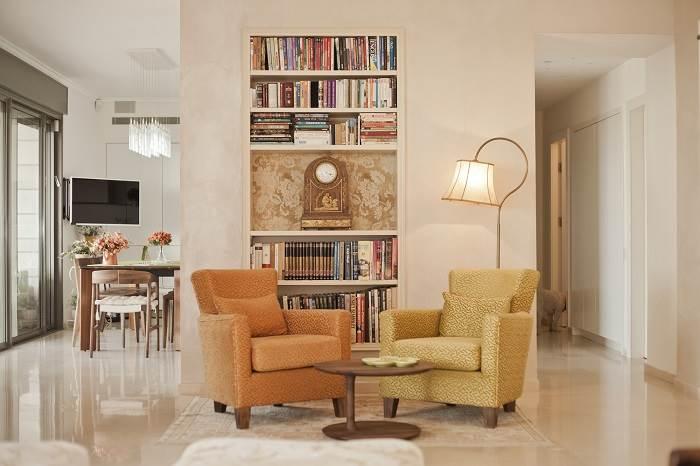 פינת קריאה עם קיר ספרים שמסתיר את המטבח ומאפשר פרטיות בין שני העולמות | צילום: גיא הכט