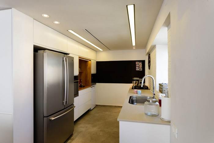 להשלמת הקו העיצובי נבחרו לחיפוי המטבח שיש מסוג גרניט פורצלן בגוון אפור, הממשיך את המראה הנקי | צילום