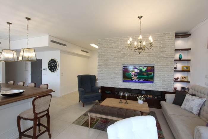 קיר הטלוויזיה בסלון חופה באבני בריקים מפירוק וכולל קמין באורך 2 מטר | עיצוב פנים: איריס מחרז | צילום: אורי סיון